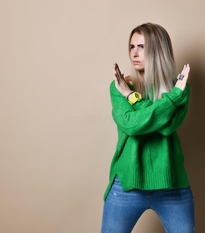 Het portret van ernstige, ongelukkige, zekere blondevrouw die twee wapens houden kruiste, gesturing geen teken, kijkend weg camer stock afbeeldingen