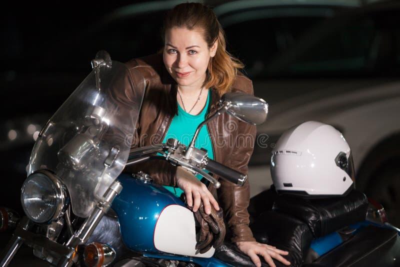 Het portret van het fietsermeisje, jongelui zwaar-gebouwde vrouw zich dichtbij haar motorfiets bevinden en witte helm die in donk royalty-vrije stock afbeelding