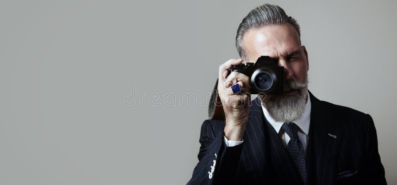Het portret van gebaarde heer maakt de foto op a stock foto