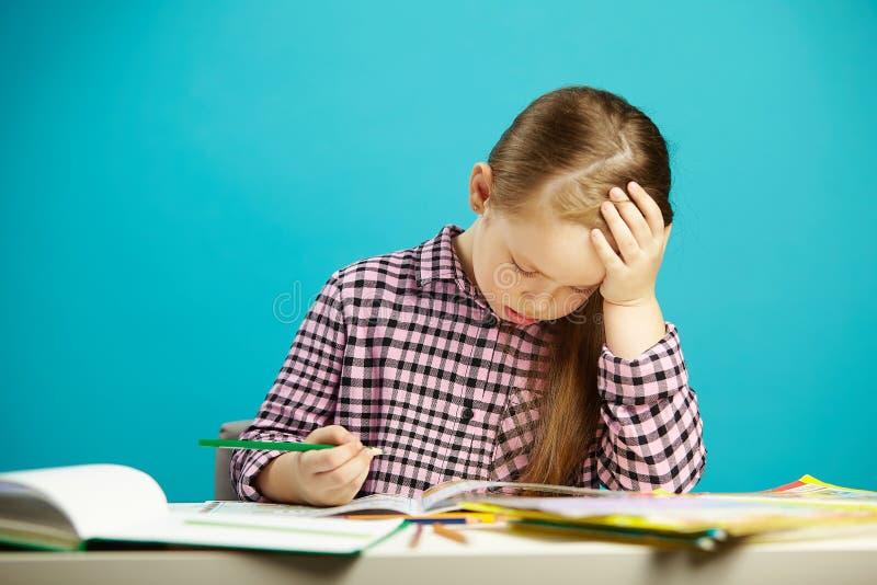 Het portret van gefrustreerd meisje bij bureau met handboeken, drukt over moeheid en teleurstelling, gezette hand aan uit hoofd,  royalty-vrije stock foto's