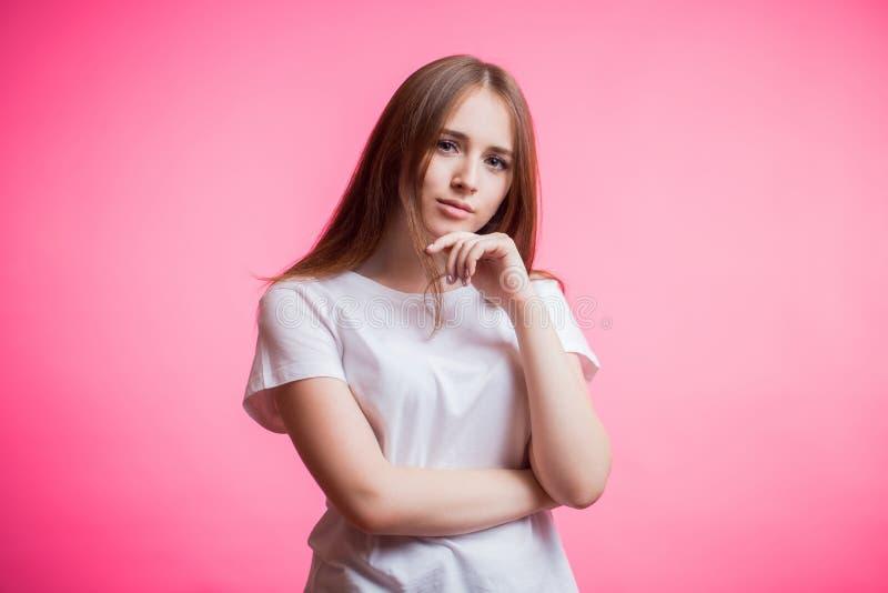 Het portret van gelukkig gembermeisje draagt het witte overhemd en het glimlachen bekijken camera op een roze achtergrond met een royalty-vrije stock foto