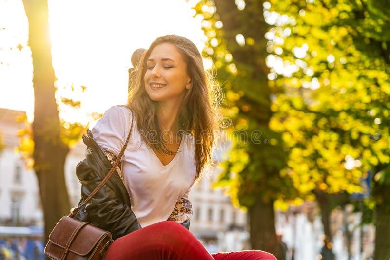 Het portret van gelukkig meisje zit in de zon, knippert haar ogen en het glimlachen in openlucht met backlight royalty-vrije stock fotografie