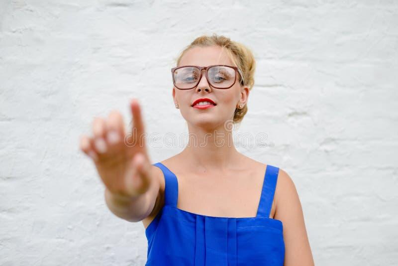 Het portret van gelukkig mooi blondemeisje met dient wat betreft beweging, op witte close-up in als achtergrond royalty-vrije stock fotografie
