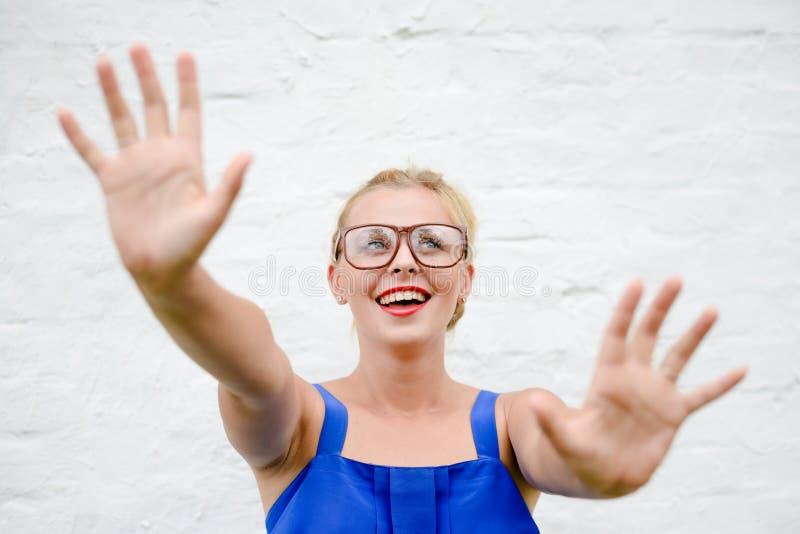 Het portret van gelukkig mooi blondemeisje werpt op haar indient het grijpen beweging stock afbeelding