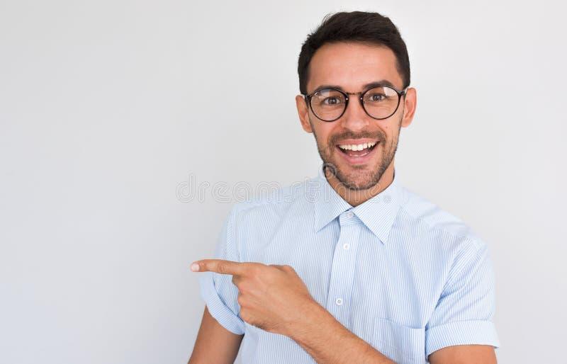Het portret van gelukkig ongeschoren knap mannetje die opzij met toothy glimlach, punten glimlachen die, aan de camera kijken, to stock afbeelding