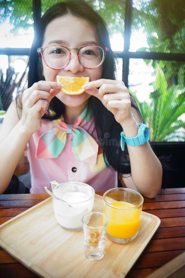 Het portret van gelukkige Aziatische vrouw in een koffie met oranje vruchten tegen van een mond zoals een glimlach, zegt kaasconc royalty-vrije stock foto's