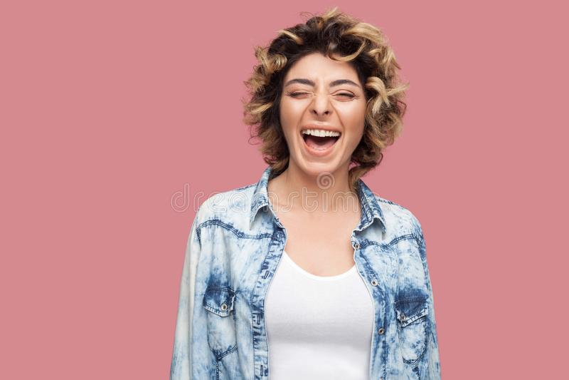 Het portret van gelukkige gelach jonge vrouw met krullend kapsel in toevallig blauw overhemd die, clossed ogen en het bekijken ca stock foto