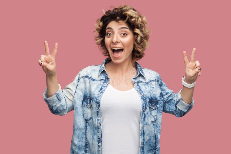 Het portret van gelukkige grappige jonge vrouw met krullend haar in toevallig overhemd die zich met overwinning bevinden of de vr royalty-vrije stock foto