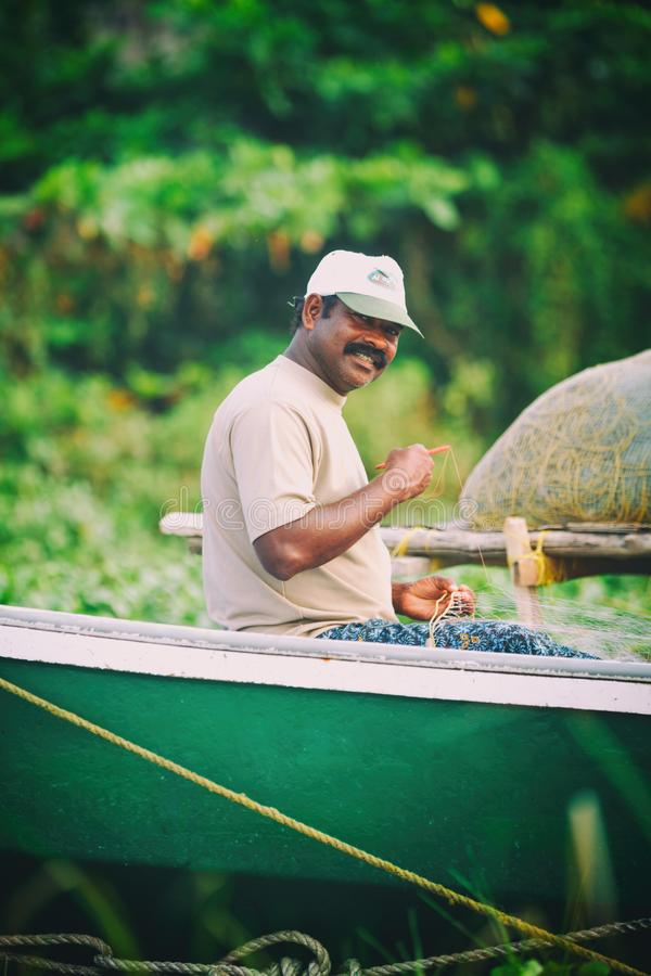 Het portret van gelukkige Indische visser ontrafelt visnetten en pakt terwijl het zitten in een boot, de Visserijgolf van Kerala  royalty-vrije stock fotografie