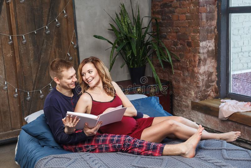 Het portret van gelukkige jonge familie heeft een rust in de slaapkamer, in nachtkleding spreekt het holdingsalbum en glimlacht t royalty-vrije stock foto's