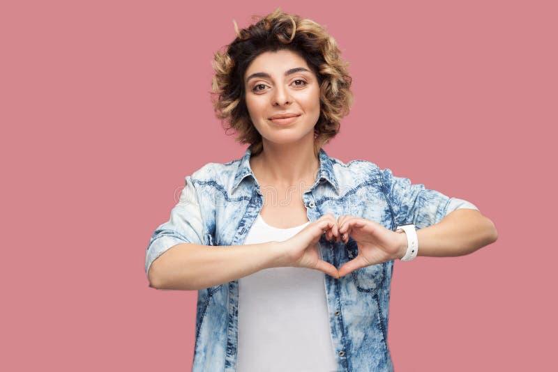 Het portret van gelukkige jonge vrouw met krullend kapsel in toevallig blauw overhemd die zich met harthanden bevinden geeft geba royalty-vrije stock fotografie