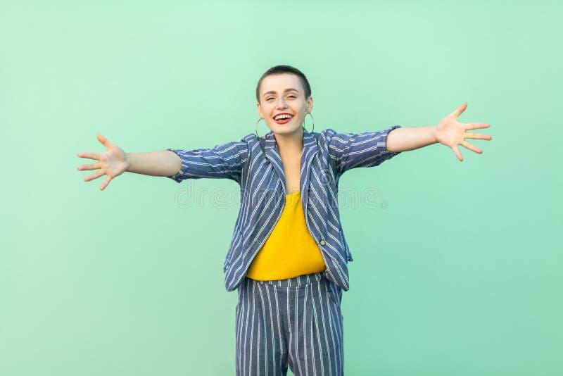 Het portret van gelukkige knappe mooie korte haar jonge modieuze vrouw in toevallig gestreept kostuum die zich met opgeheven wape stock foto
