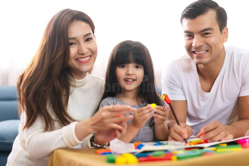 Het portret van het gelukkige meisje van de familiedochter leert om het kleurrijke stuk speelgoed van plasticineblokken samen met royalty-vrije stock afbeelding