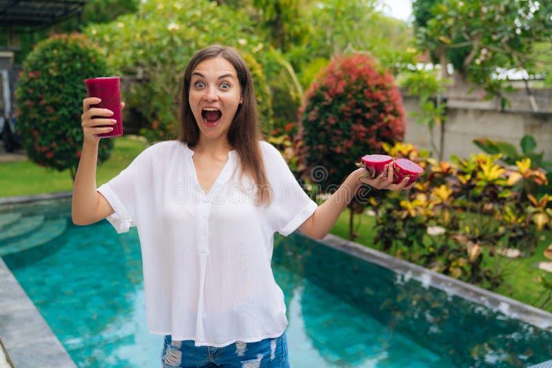 Het portret van gelukkige vrouw drukt positief uit en houdt in hand dichtbijgelegen pool van het draakfruit stock foto