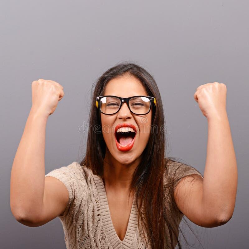 Het portret van gelukkige vrouw jubelt pompende extatische vuisten viert succes tegen grijze achtergrond stock afbeelding
