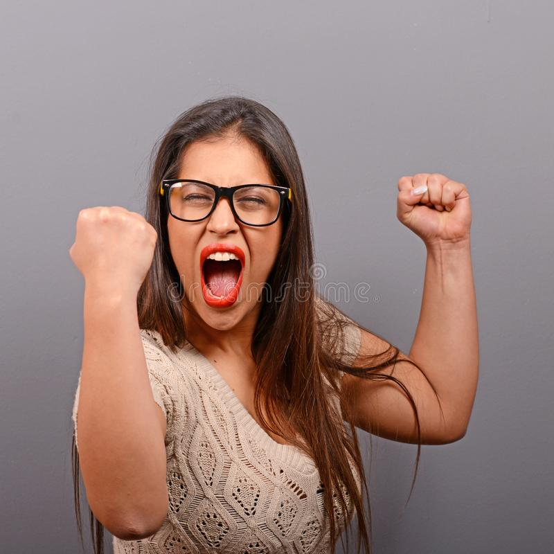 Het portret van gelukkige vrouw jubelt pompende extatische vuisten viert succes tegen grijze achtergrond stock fotografie