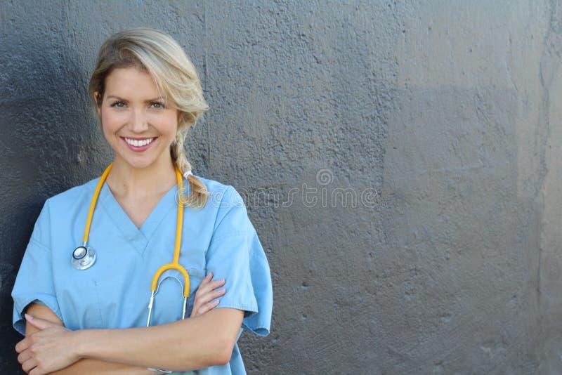 Het portret van gelukkige vrouwelijke verpleegster met stethoscoop bevindende wapens kruiste geïsoleerd over donkergrijze achterg royalty-vrije stock afbeeldingen