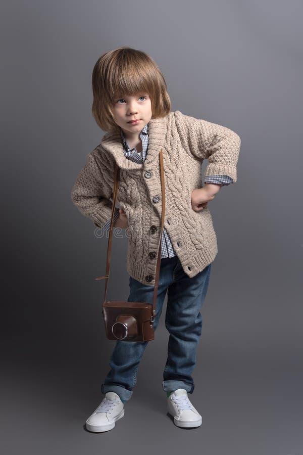 Het portret van gemiddelde lengte van een kleine jongen in een gebreide cardigan met een uitstekende filmcamera stock foto