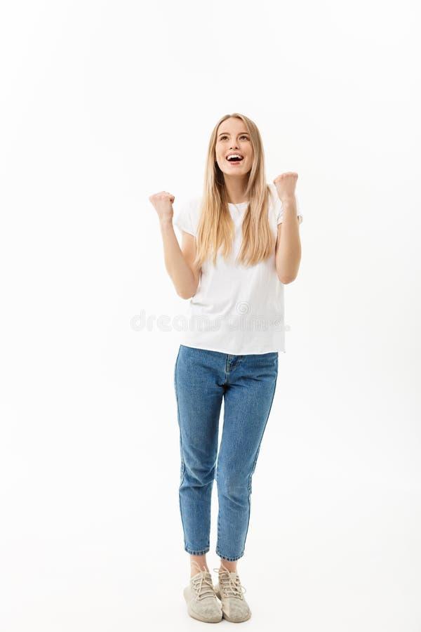 Het Portret van gemiddelde lengte van een vrolijke vrouw in wit overhemd en Jean die haar succes over witte achtergrond vieren stock fotografie