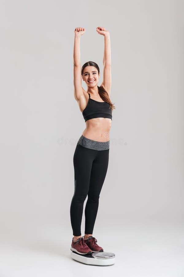 Het portret van gemiddelde lengte van gelukkige gymnastiek- vrouw die haar weig meten stock afbeelding