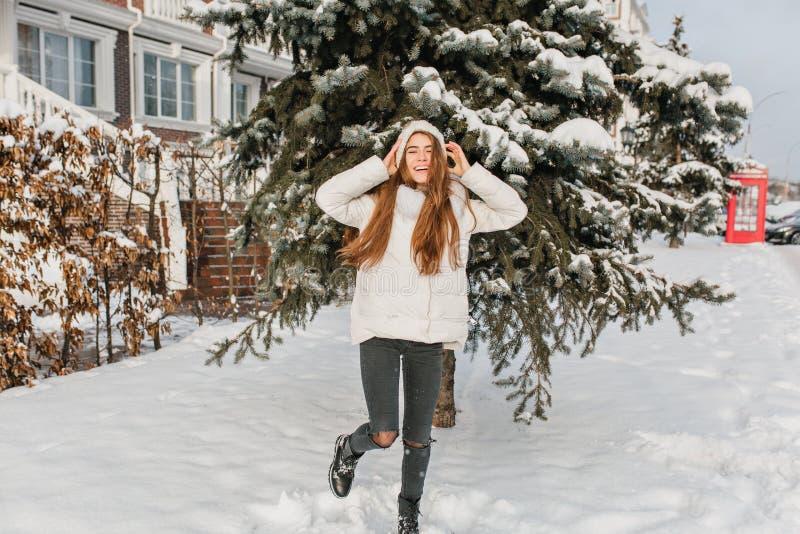 Het portret van gemiddelde lengte van ontspannen blondemeisje in zwarte broek die bij sneeuwstraat met glimlach dansen Openluchtf royalty-vrije stock foto