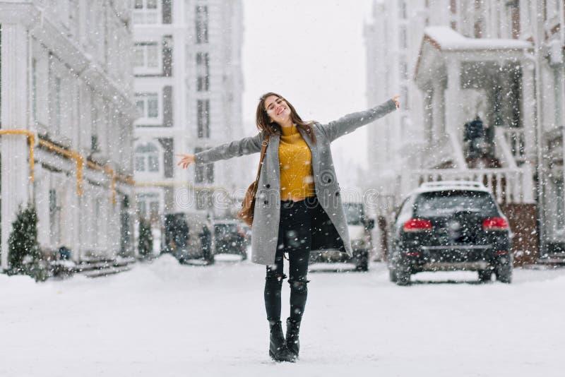 Het portret van gemiddelde lengte van romantische Europese dame draagt lange laag in sneeuwdag Openluchtfoto van geïnspireerde do stock afbeelding