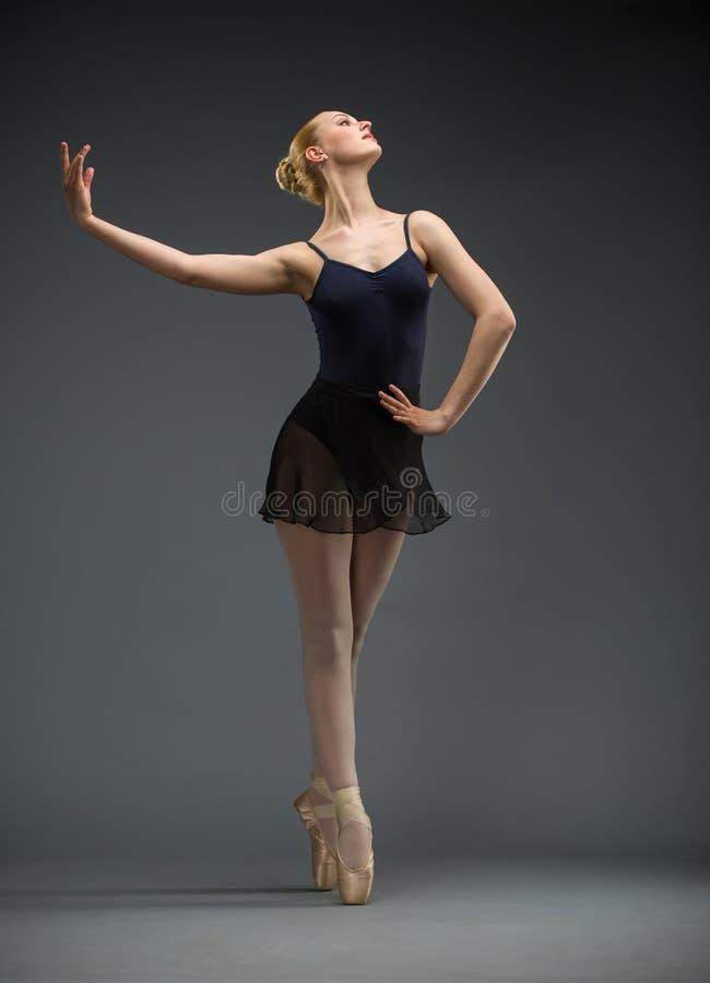 Het portret van gemiddelde lengte van dansende ballerina met hand op heupen royalty-vrije stock foto