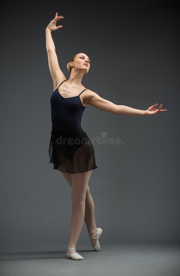 Het portret van gemiddelde lengte van dansende ballerina met uitgestrekte wapens stock foto