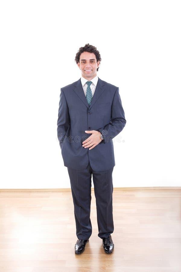 Het portret van gemiddelde lengte van het glimlachen zakenman status stock afbeelding