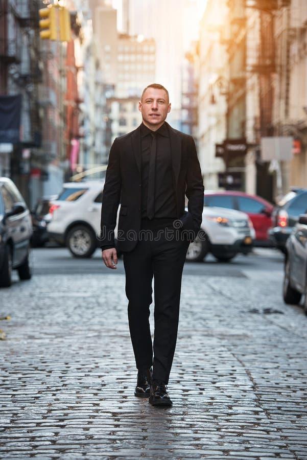 Het portret van gemiddelde lengte van het volwassen zakenman lopen op stadsstraat die zwart kostuum dragen royalty-vrije stock afbeeldingen