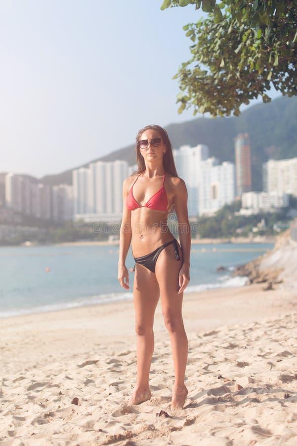 Het portret van gemiddelde lengte van zeker geschiktheids vrouwelijk model dragend zwempak die zich op zandig strand met hoge bin royalty-vrije stock afbeelding
