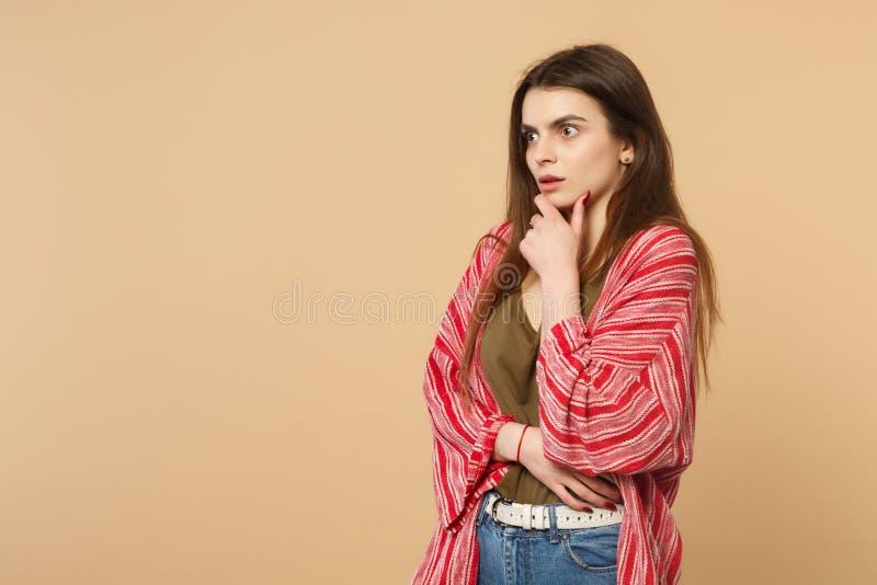Het portret van geschokte jonge vrouw die in die vrijetijdskleding, zette handsteun op kin op opzij kijken op pastelkleurbeige wo royalty-vrije stock fotografie