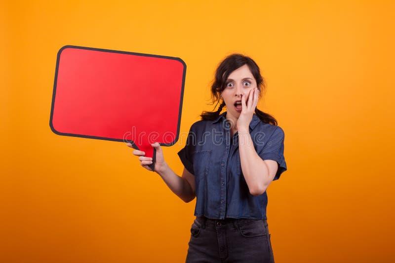 Het portret van het geschokte mooie vrouw leeg houden denkt bel in studio over gele achtergrond stock foto