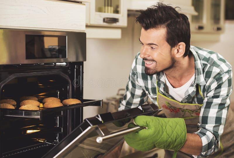Het portret van het glimlachen van het dienblad van de mensenholding van bakt thuis in keuken stock afbeeldingen