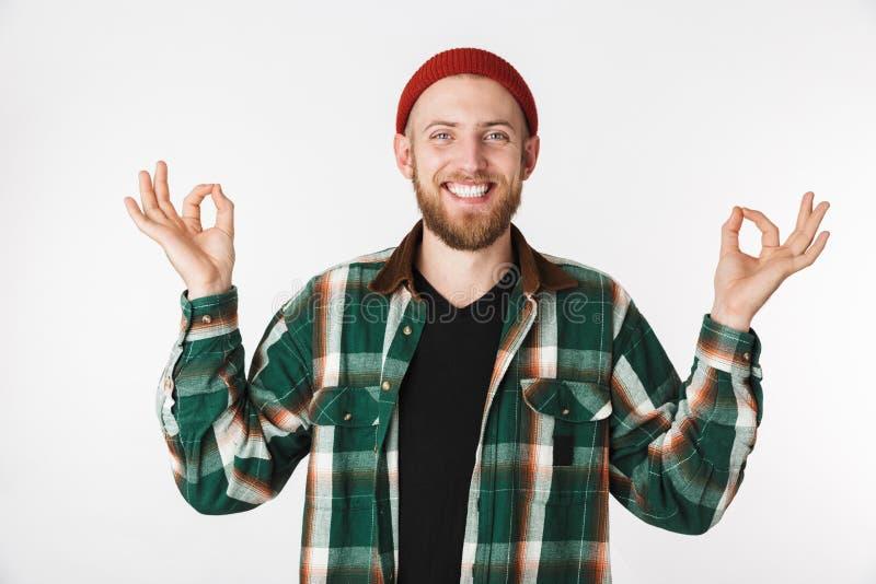 Het portret van het glimlachen van gebaarde kerel die hoed en plaidoverhemd dragen die meditatie tonen ondertekent, terwijl statu stock afbeeldingen