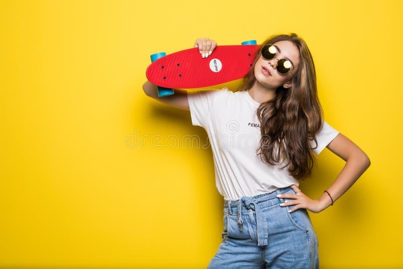 Het portret van het glimlachen wekte donkerbruine vrouwen een gat makend die skateboard op op de gele achtergrond wordt geïsoleer stock fotografie