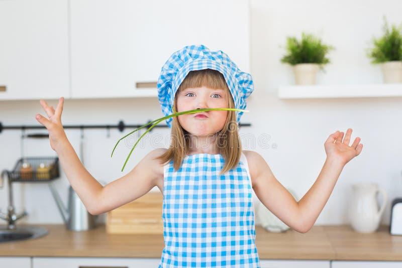Het portret van glimlachend meisje in kok kleedt zich funs met bosui op een keuken royalty-vrije stock afbeeldingen