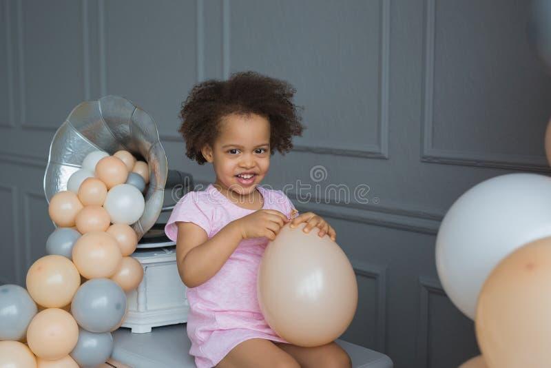 Het portret van glimlachend zwart meisje met een ballon zit op een dienst stock foto's