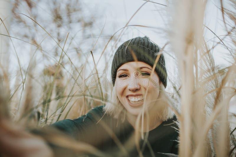 Het portret van glimlachende blondevrouw met breit hoed op omringd van rietinstallaties in aard royalty-vrije stock foto