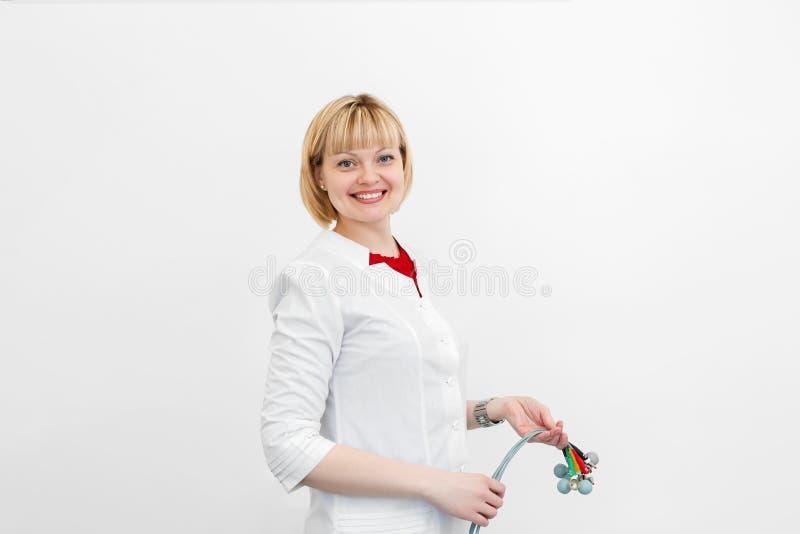 Het portret van glimlachende cardioloog houdt de elektrocardiograafsensoren in zijn handen alvorens hen met het systeem te verbin stock fotografie