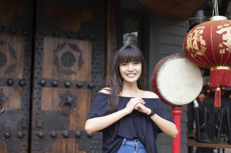 Het portret van glimlachende jonge Aziatische vrouw geniet van in de stad van China stock afbeelding