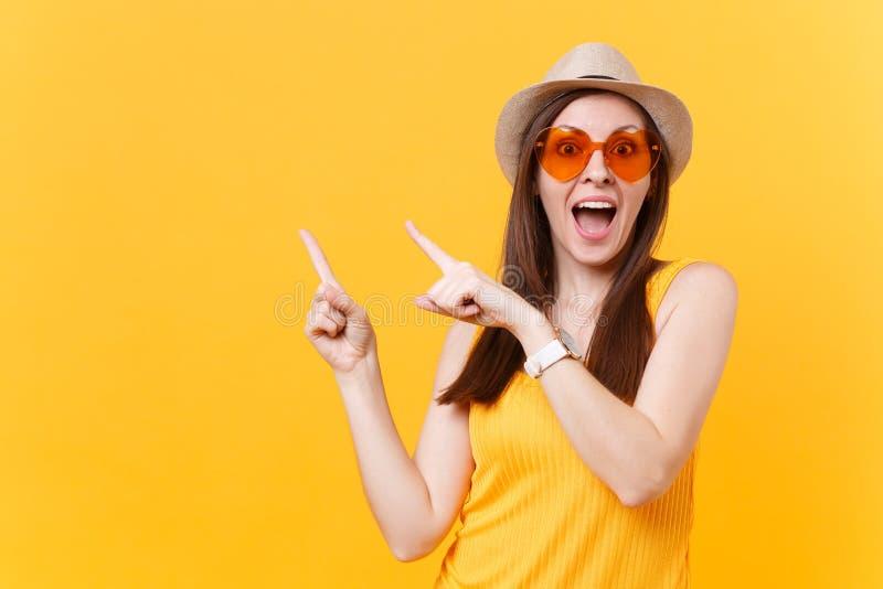 Het portret van glimlachende jonge vrouw in de hoed van de strozomer, oranje glazen die wijsvingers richten kopieert opzij geïsol stock foto