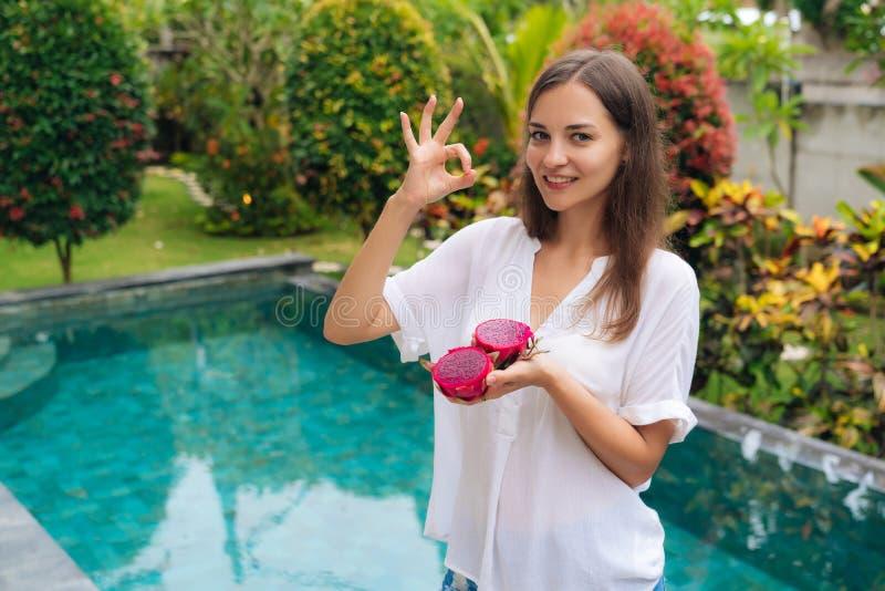 Het portret van glimlachende vrouw houdt draakfruit in hand en tonend o.k. of groot teken stock foto