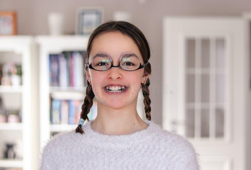 Het portret van het grappige aantrekkelijke glimlachen preteen meisje met vlechten en kunstgebits die rond het dragen van glazenb royalty-vrije stock foto