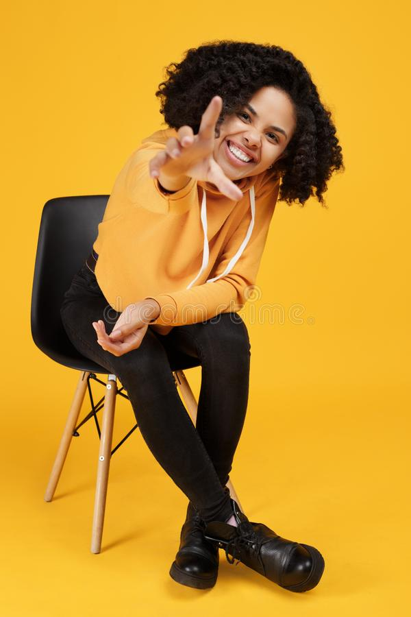 Het portret van grappige Afrikaanse Amerikaanse jonge vrouw met mooie glimlach kleedde zich in vrijetijdskleding zittend op modie royalty-vrije stock foto