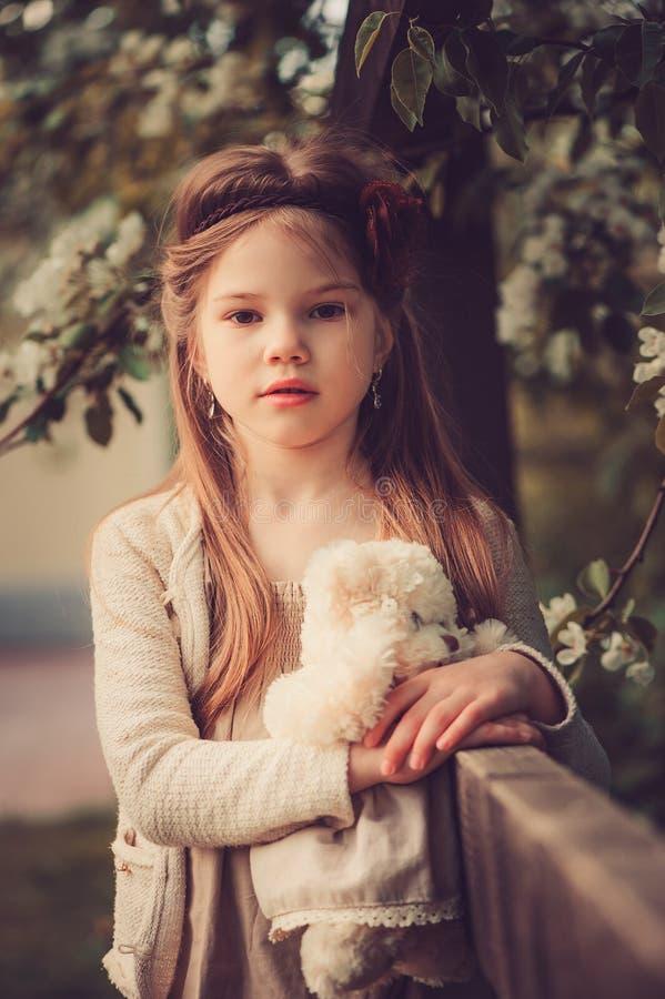 Het portret van het de lenteland van aanbiddelijk dromerig jong geitjemeisje dichtbij houten omheining met teddybeer royalty-vrije stock foto