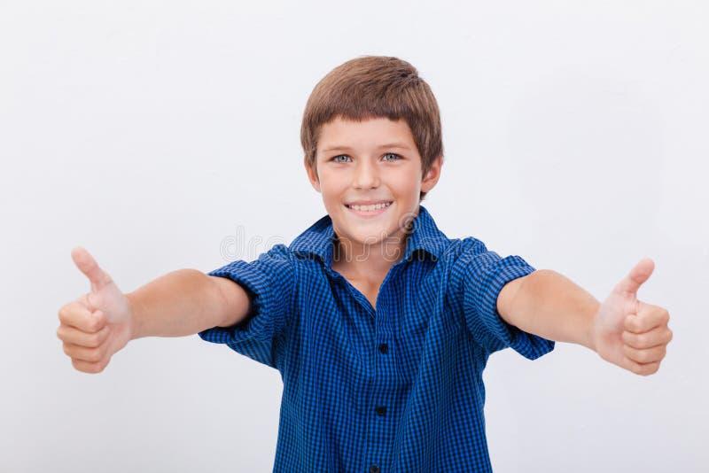 Het portret van het gelukkige jongen tonen beduimelt omhoog gebaar stock afbeelding
