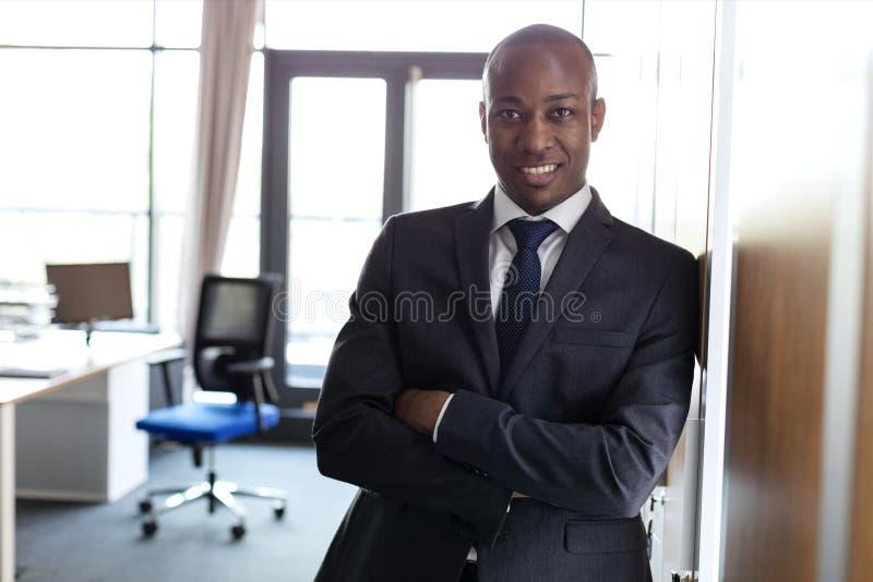 Het portret van het glimlachen jonge zakenman status bewapent het gekruiste leunen op kast in bureau stock foto's
