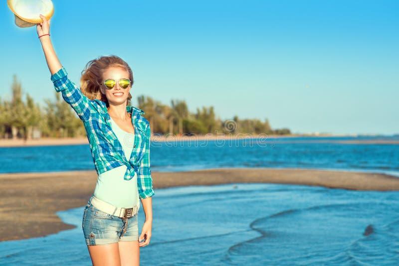 Het portret van het jonge mooie het glimlachen slanke blonde dragen weerspiegelde hart gevormde zonnebril die een hoed in haar wa stock afbeeldingen