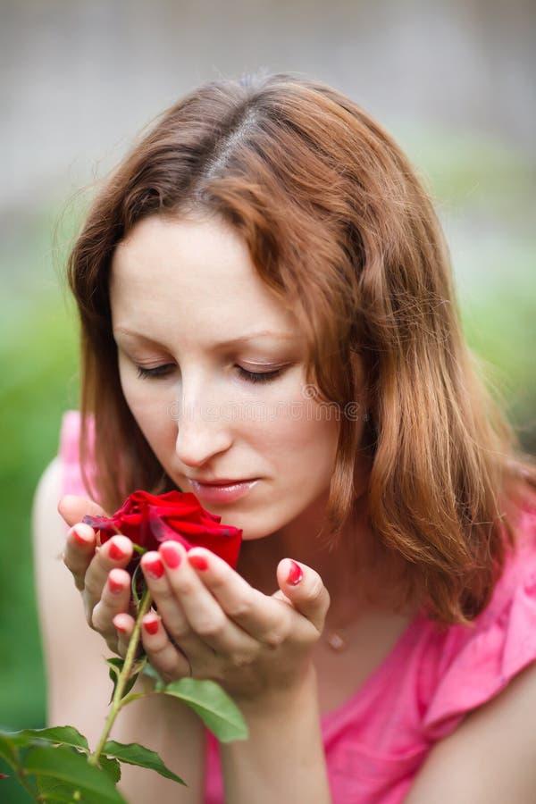 Het portret van het jonge vrouw ruiken nam in tuin toe stock afbeelding